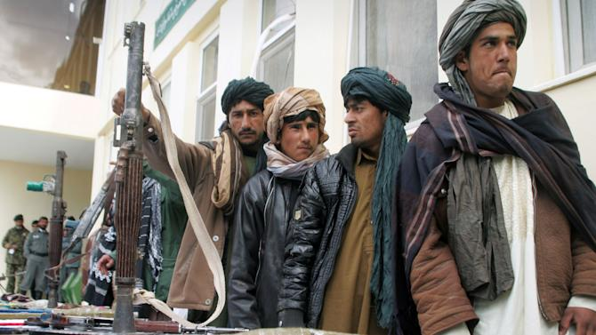 Former Taliban militants who have turned in their weapons stand during a ceremony with the Afghan government in Herat, Afghanistan, Sunday, Feb. 17, 2013. About 35 former Taliban militants from Herat province handed over their weapons as part of a peace-reconciliation program. (AP Photo/Hoshang Hoshimi)
