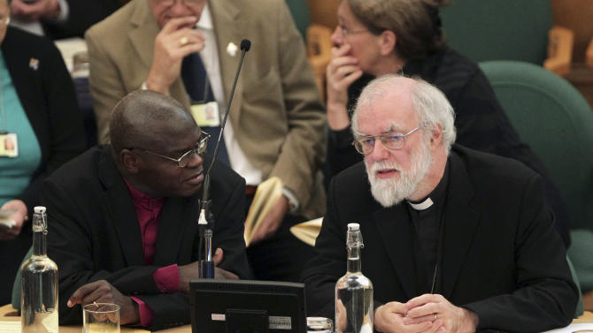Dr John Sentamu, Archbishop of York, left, and Dr Rowan Williams, the outgoing Archbishop of Canterbury, speak during a meeting of the General Synod of the Church of England, at Church House in central London, Wednesday Nov. 21, 2012. The leader of the Church of England says it has much explaining to do following its failure to vote to allow women to serve as bishops. (AP Photo/Yui Mok, Pool)
