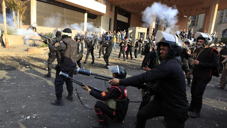 Egyptian riot police fire tear gas at protesters, not seen, during clashes in front of the Semiramis Intercontinental hotel, background near Tahrir Square, Cairo, Egypt,Tuesday, Jan. 29, 2013. Since Saturday, the Nile-side Semiramis Intercontinental has been on the front line of clashes between riot police and angry youths, with both sides throwing stones at each other along the city's famed Corniche promenade while tear gas wafted several stories up inside the building. (AP Photo/Khalil Hamra)