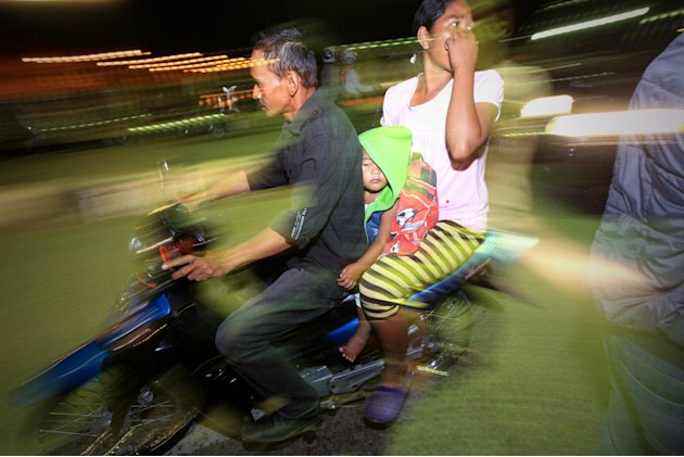 People on motorcycles flee after a strong earthquake hit in Aceh, Indonesia, Tuesday, Jan. 22, 2013.  A strong, shallow earthquake rocked parts of western Indonesia early Tuesday, killing a 9-year-old