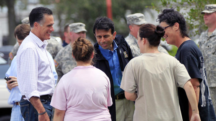In this Aug. 31, 2012, photo, Republican presidential candidate Mitt Romney, left, and Louisiana Gov. Bobby Jindal, center, greet residents displaced by Isaac in Lafitte, La. President Barack Obama tweaked his travel plans to head to Louisiana on Monday, Sept. 3, 2012, to see the damage from Hurricane Isaac ahead of his own nominating convention_ shortly after Republican presidential candidate Mitt Romney toured the area. (AP Photo/Gerald Herbert)