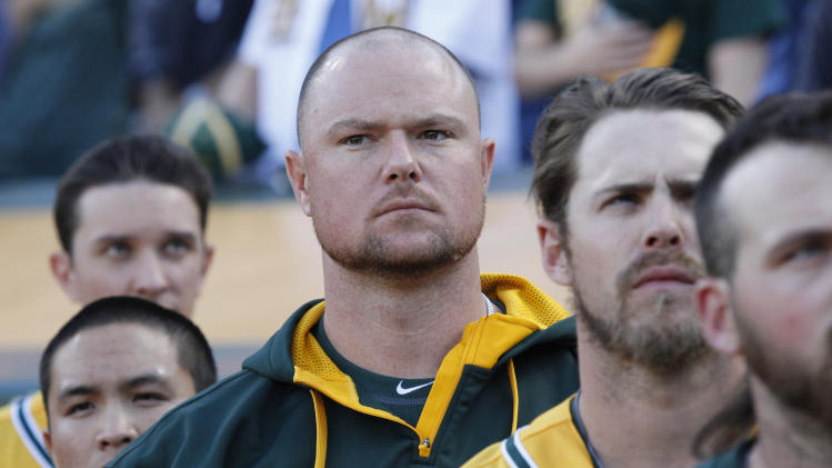 Oakland Athletics new acquisition Jon Lester, center, stands at the dugout during the playing of the national anthem before a baseball game against the Kansas City Royals Friday, Aug. 1, 2014 in Oakland, Calif. The Athletics acquired Lester and Gomes from the Boston Red Sox for outfielder Yoenis Cespedes. (AP Photo/George Nikitin)