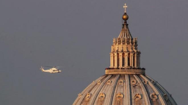 A helicopter carrying Pope Benedict XVI passes St. Peter's Basilica on its way out of Vatican City.