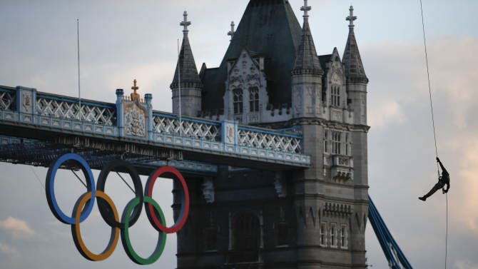 British Royal Marine Martyn Williams, right, rappels down from a Royal Navy Sea King helicopter into the Tower of London with the Olympic torch, Friday, July 20, 2012, in London. The Olympic Torch arrived in London after it was carried around England in a relay of torchbearers to make its way to the London 2012 Olympic Games opening ceremony on July 27, 2012. (AP Photo/Jae C. Hong)