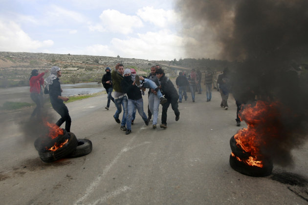 Palestinians carry an injured person during clashes with Israeli troops, outside Ofer, an Israeli military prison near the West Bank city of Ramallah, Friday, Feb. 15, 2013. Palestinian demonstrators clashed with Israeli soldiers on Friday at a rally held in support of a prisoner observing an intermittent hunger strike to protest his incarceration. The Israeli military said about 200 Palestinians threw rocks at soldiers who responded with tear gas during the rally outside Ofer prison in the West Bank. The protesters called for the release of Samer Issawi, who has been on an on-again, off-again hunger strike for several months as he serves time for alleged terror activity. (AP Photo/Majdi Mohammed)