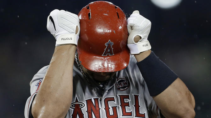 File-This June 25, 2013 file photo shows Los Angeles Angels' Albert Pujols hitting his helmet as he reacts to flying out against the Detroit Tigers in the seventh inning of a baseball game in Detroit. Pujols is done for the season because of an injured left foot. The Angels made the announcement Monday Aug. 19, 2013 before playing Cleveland. Pujols hasn't played since July 26. He had been saying he wanted to return when his partially torn plantar fascia healed. (AP Photo/Paul Sancya, File)