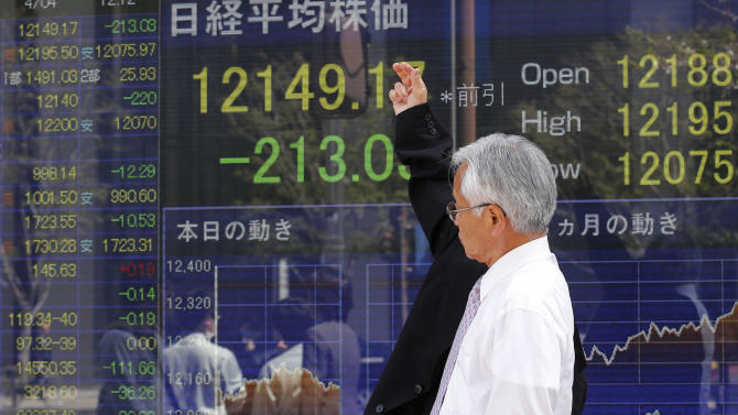 A man looks at the latest Nikkei index and other stock information on display in an electric signboard of a securities firm in Tokyo Thursday, April 4, 2013. Weak economic reports on hiring and service industry growth in the U.S. sent Asian stock markets lower Thursday. (AP Photo/Koji Sasahara)