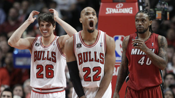 Chicago Bulls forward Taj Gibson (22) and guard Kyle Korver (26) react to a foul call during the third quarter of Game 5 of the NBA basketball Eastern Conference finals Thursday, May 26, 2011, in Chicago. At right is Miami Heat's Udonis Haslem. (AP Photo/Nam Y. Huh)