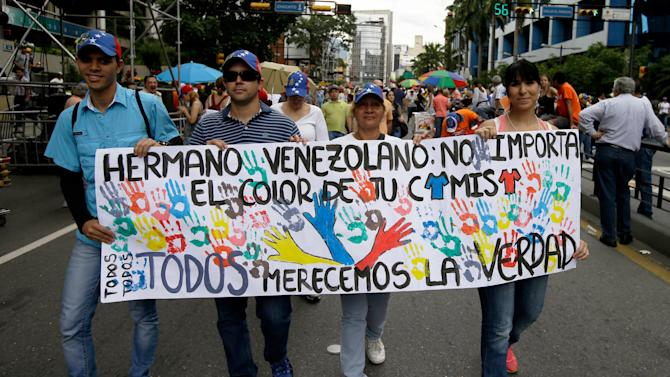 """In this May 1, 2013 photo, supporters of the opposition march with a banner that reads in Spanish; """"Venezuelan brother: The color of your shirt does not matter, we all deserve the truth,"""" during a May Day march in Caracas, Venezuela. Husbands and wives, brothers and sisters, parents and children find themselves on opposite sides of the bitter fight between Nicolas Maduro, whose supporters tend to wear the color red, and an opposition that accuses the socialist government of using fraud and intimidation to win the presidency. (AP Photo/Fernando Llano)"""