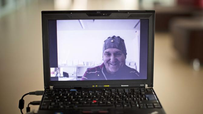 Mark-Andre Duc, a partially tetraplegic patient, is seen on a laptop screen as he talks to scientists in Switzerland's Federal Institute of Technology in Lausanne, Switzerland, Tuesday, April 24, 2012. From a hospital 100 kilometers (62 miles) away, he imagined lifting his fingers to direct a robot. Swiss scientists demonstrated with this test how a partially paralyzed person can control a robot using brain signals alone. (AP Photo/Anja Niedringhaus)