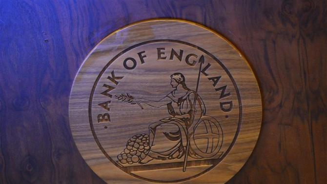 A wooden carving of the Bank of England logo is seen on a desk during the bank's quarterly inflation report news conference at the Bank of England in London