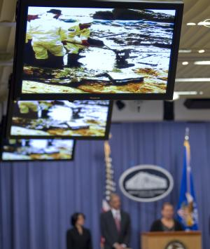 Photographs of workers cleaning oil soaked beaches are shown during a news conference at the Justice Department in Washington, Wednesday, Dec. 15, 2010, where Attorney General Eric Holder announced a civil lawsuit against nine defendants for the Deepwater Horizon oil spill.  (AP Photo)