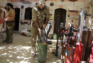 A Free Syrian Army fighter prepares a homemade shell…