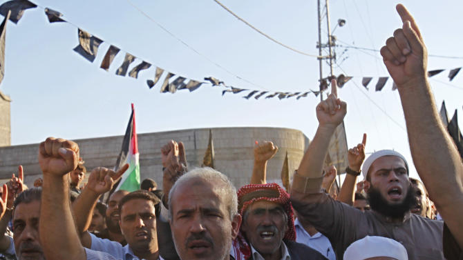 Supporters of the Palestinian militant group, Islamic Jihad, which is opposed to peace talks with Israel, raise their fists while chanting Islamic slogans during a rally marking the 13th anniversary of the Al-Aqsa Intifada or uprising, in the Jabaliya Refugee Camp, northern Gaza Strip, Thursday, Sept. 26, 2013. Israeli and Palestinian negotiators have agreed to intensify peace talks aimed at reaching a final peace agreement, not an interim accord, U.S. Secretary of State John Kerry said on Wednesday. (AP Photo/Adel Hana)