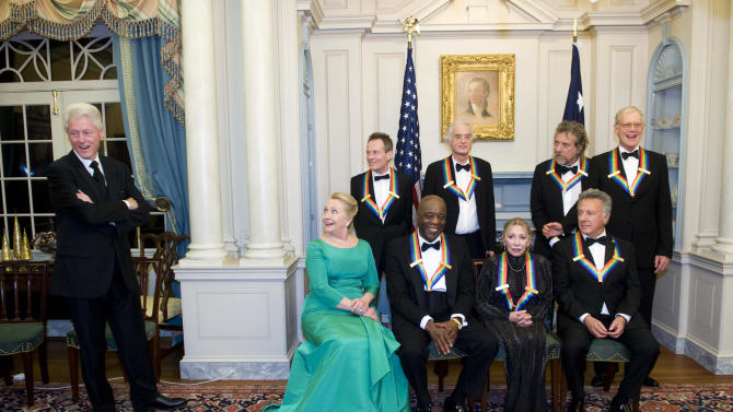 The 2012 Kennedy Center Honorees and Secretary of State Hillary Rodham Clinton, second from left, wait for former President Bill Clinton, left, to join them for a group photo after the State Department Dinner for the Kennedy Center Honors gala Saturday, Dec. 1, 2012 at the State Department in Washington. The 2012 Kennedy Center Honorees are, from left, John Paul Jones, Buddy Guy, Jimmy Page, Natalia Makarova, Robert Plant, Dustin Hoffman, and David Letterman. (AP Photo/Kevin Wolf)