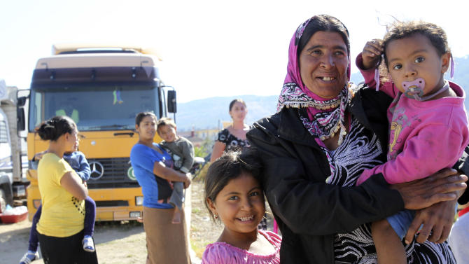 A gypsy woman holding her child poses for photos at a gypsy camp near the town of Farsala, some 280 km ( 173 miles) north of Athens, Greece, on Sunday, Oct. 20 , 2013. Greek authorities on Friday, Oct. 18, 2013 have requested international assistance to identify the four-year-old girl found living in a Gypsy camp with a couple arrested and charged with abducting her from her birth parents. A police statement says the child was located Wednesday, Oct. 17, 2013 near the town of Farsala, central Greece, during a nationwide crackdown on illegal activities in Gypsy camps. (AP Photo/Nikolas Giakoumidis)