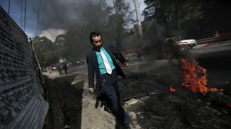 "A man walks past burning tires in front of the ""Linda Vista"" slum during a protest against the eviction of residents occupying the slum, in Guatemala City"