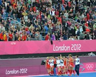 Britain's players celebrate after their women's field hockey preliminary round match between Belgium and Great Britain at the Riverbank Arena in London during the London 2012 Olympic Games. Great Britain won 3-0