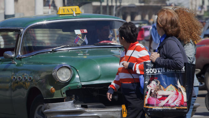 Women cross the street in front of moving traffic in Havana, Cuba, Monday, March 4, 2013.  Cuban law prescribes jail time for motorists who kill pedestrians, even if they aren't speeding and the victim crosses improperly. (AP Photo/Ramon Espinosa)