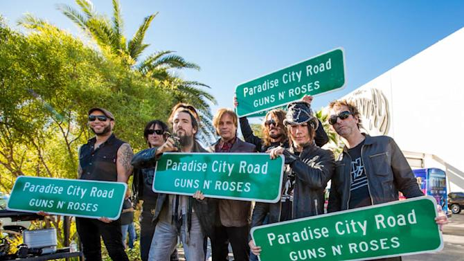 "In this Monday Oct. 29, 2012 photo provided by Erik Kabik, from left, Frank Ferrer, Richard Fortus, Bumblefoot, Chris Pitman, Dizzy Reed, DJ Ashba, and Tommy Stinson attend a ceremonial street renaming of Paradise Road to Paradise City Road in Las Vegas. A county commissioner in Las Vegas says she regrets the board temporarily renamed a street in honor of Guns N' Roses after finding out about the band's suggestive publicity artwork. Ads promoting the band's four-week run at the Hard Rock Hotel & Casino depict a disheveled woman who appears to be sexually assaulted beneath the iconic ""Welcome to Fabulous Las Vegas"" sign. (AP Photo/Courtesy Erik Kabik)"