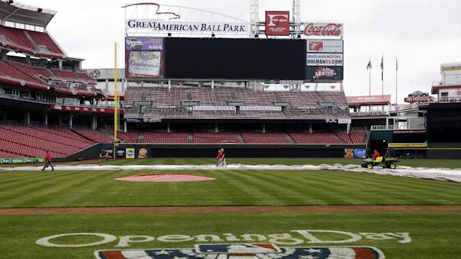 Cincinnati Reds grounds crew members prepare the field ready at Great American Ball Park for Monday's opening day baseball game against the Los Angeles Angels, Sunday, March 31, 2013, in Cincinnati. (AP Photo/Al Behrman)