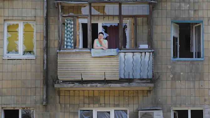 A local woman stands on her damaged balcony after morning shelling in Donetsk, eastern Ukraine, Saturday, Aug. 9, 2014. Several shells fell this morning in a northern Donetsk neighborhood, near the airport. No human casualties were registered. (AP Photo/Sergei Grits)