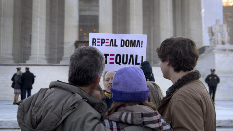 "FILE - In this March 27, 2013, file photo a woman holds up a sign that reads ""REPEAL DOMA,"" the Defense of Marriage Act in front of a group from Alabama, clasped in prayer in front of the Supreme Court in Washington, as the court hears arguments on gay marriage. Sometime this early July, the Court will announce the outcomes in cases on Californian's ban on same-sex marriage, Proposition 8, and the federal Defense of Marriage Act, the federal law that defines marriage as the union of a man and a woman. (AP Photo/Carolyn Kaster, File)"