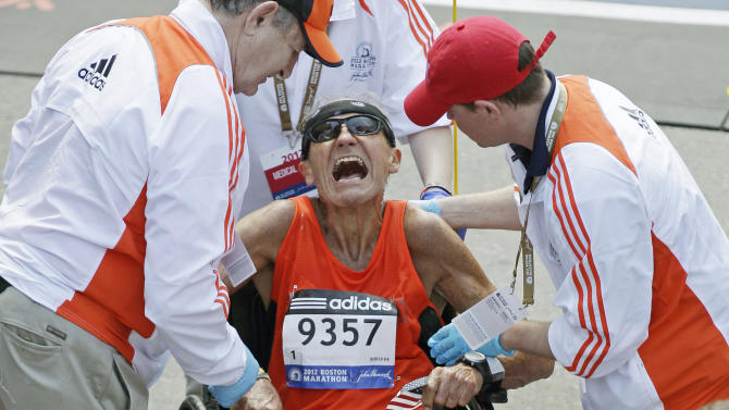 John Ouweleen, 71, of Sebastian, Fla., is helped by medical workers as he cramped up after finishing the 116th Boston Marathon in Boston, Monday, April 16, 2012. It was the second-slowest Boston race since 1985, as temperatures rising into the 80s slowed the leaders and may have convinced as many as 4,300 entrants to sit this one out.  (AP Photo/Charles Krupa)