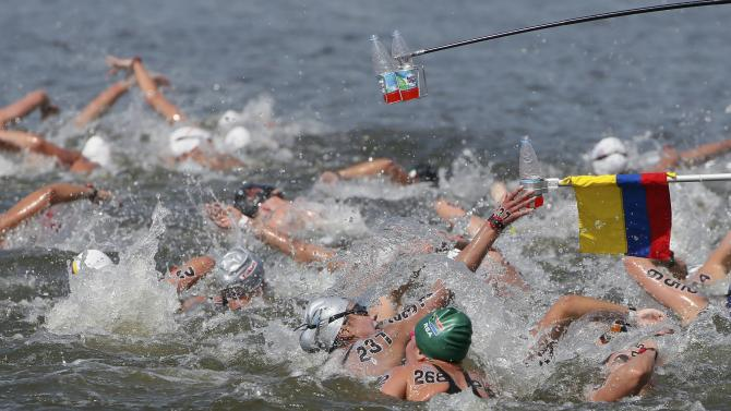 Caldas Calle of Ecuador and other swimmers reach out for drinks during the women's 10km open water race at the Aquatics World Championships in Kazan