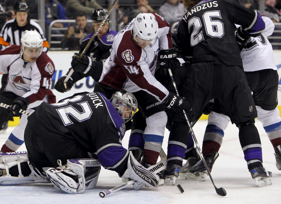 Los Angeles Kings goalie Jonathan Quick (32) makes a save on a shot as Colorado Avalanche right wing David Jones (54) tries to get the rebound in the third period of an NHL hockey game in Los Angeles, Saturday, Feb. 26, 2011. The Kings won the game 4-3. (AP Photo/Alex Gallardo)