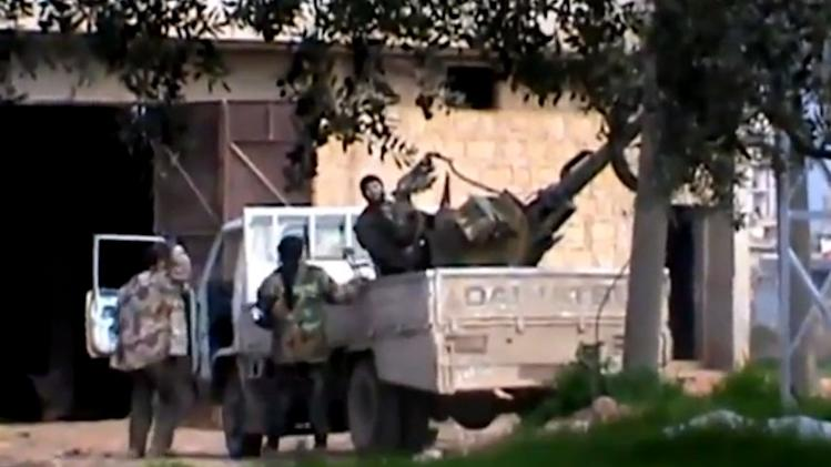 In this image taken from video obtained from the Shaam News Network, which has been authenticated based on its contents and other AP reporting, A Free Syrian Army fighter stands on a vehicle as he holds his weapon in Taftanaz village, Idlib province, northern Syria, on Wednesday, Jan. 2, 2013. Rebels attacked a sprawling air base on Wednesday as the opposition expanded its offensive on military airports in an attempt to sideline a major weapon in the hands of President Bashar Assad's forces. The Observatory said the rebel assault on the Taftanaz base was preceded by heavy shelling of the area, and the fighters appeared to be trying to storm the facility. (AP Photo/Shaam News Network via AP video)