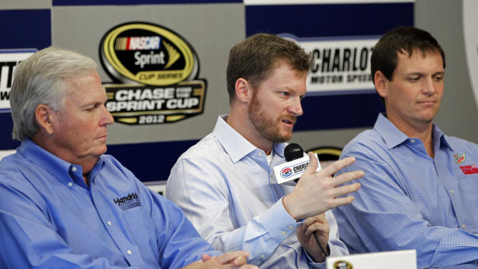 Dale Earnhardt Jr, center, talks about missing the next two races with his second concussion in the past six weeks as team owner Rick Hendrick, left, and crew chief Steve Letarte, right, look on  during a news conference prior to practice for Saturday's NASCAR Bank of America 500 NASCAR Sprint Cup series auto race in Concord, N.C., Thursday, Oct. 11, 2012. (AP Photo/Terry Renna)