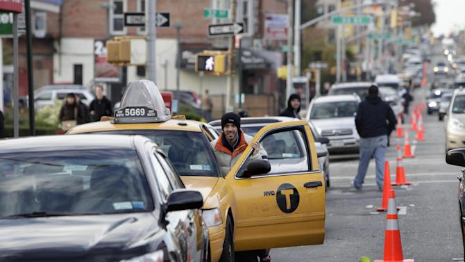 A cab driver pushes his taxi cab forward in a line for gasoline in the Brooklyn borough of New York, Friday, Nov. 2, 2012.   In parts of New York and New Jersey, drivers face another day of lining up for hours at gas stations struggling to stay supplied.  Superstorm Sandy damaged ports that accept fuel tankers and flooded underground equipment that sends fuel through pipelines. Without power, fuel terminals can't pump gasoline onto tanker trucks, and gas stations can't pump fuel into customers' cars.  (AP Photo/Seth Wenig)