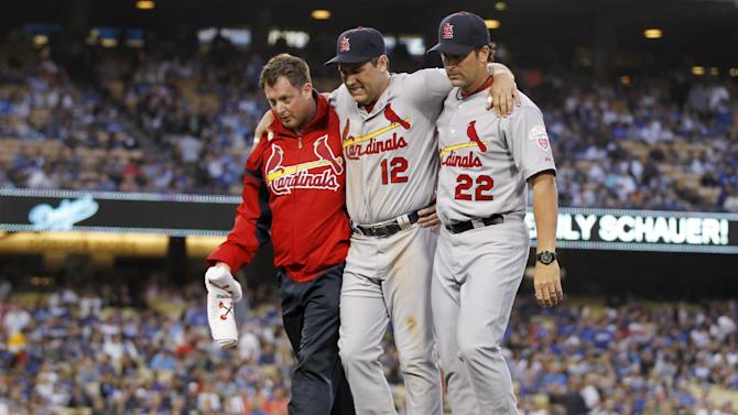 St. Louis Cardinals first baseman Lance Berkman, center, is helped off the field by a trainer and manager Mike Matheny, right, after sustaining an injury while forcing out Los Angeles Dodgers' Justin Sellers at first base to end the second inning of a baseball game on Saturday, May 19, 2012, in Los Angeles. (AP Photo/Danny Moloshok)