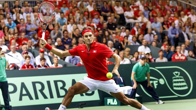 Roger Federer, of Switzerland, returns a ball to Fabio Fognini, of Italy, during the third single match of the tennis Davis Cup World Group semifinal  between Switzerland and Italy,  in Geneva, Switzerland, Sunday, Sept. 14, 2014.  Roger Federer has taken Switzerland to its first Davis Cup final in 22 years, beating Fabio Fognini of Italy in the opening reverse singles Sunday for a winning 3-1 lead in their semifinal. (AP Photo/Keystone,Salvatore Di Nolfi)