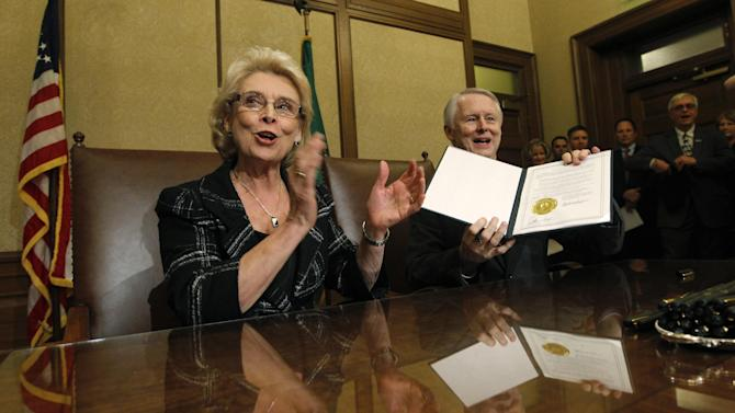 Gov. Chris Gregoire, left, applauds as Secretary of State Sam Reed holds up the signed certification of Referendum 74,  a citizen-passed measure that legalizes same-sex marriage in the state, Wednesday, Dec. 5, 2012, in Olympia, Wash. Gregoire and Reed both signed the document at the signing ceremony, which allows gay couples to marry beginning Dec. 9. (AP Photo/Elaine Thompson)