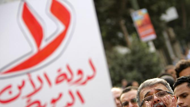 "An Egyptian protester shouts slogans as another holds anti-Muslim brotherhood banner reading, ""no for bloody state security,"" during a protest in support of victims of Friday's clashes in the Nile Delta city of Mansoura, in Cairo, Egypt, Saturday, March 2, 2013. (AP Photo/Amr Nabil)"