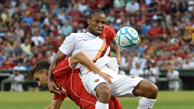 Liverpool's Fabio Borini (L) tussles with Roma's Seydou Keita during a friendly soccer match between Liverpool and Roma at Fenway Park, Boston on July 23, 2014