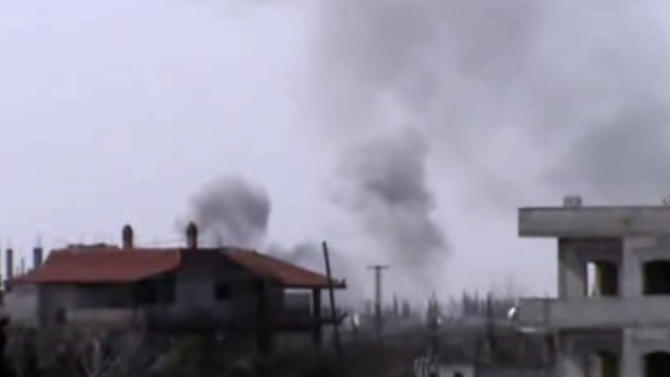 In this image taken from video obtained from the Shaam News Network, which has been authenticated based on its contents and other AP reporting, smoke rises after warplanes shell the town of Jobar, in Homs, Syria, on Thursday, Jan. 24, 2013. (AP Photo/Shaam News Network via AP video)
