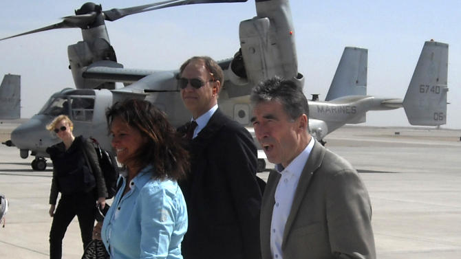 NATO Secretary-General Anders Fogh Rasmussen, right, arrives with his wife Mette Rasmussen, center, to Camp Bastion, Helmand, Afghanistan, Tuesday, March 5, 2013. NATO's chief is embracing a proposal to keep 352,000 Afghans in uniform through 2018 — about 122,000 more than originally planned. (AP Photo/Kimberly Dozier)