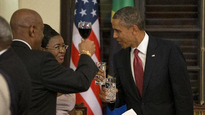 President Barack Obama toasts with Tanzanian first lady Salma Kikwete during an official dinner at the State House in Dar Es Salaam, Tanzania, Monday, July 1, 2013. The president is traveling in Tanzania on the final leg of his three-country tour in Africa. (AP Photo/Evan Vucci)