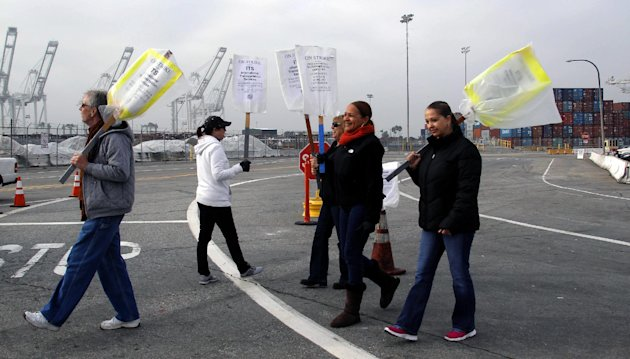 Clerical workers carry signs in protest at the Port of Long Beach, Calif. on Tuesday, December 4, 2012. Los Angeles Mayor Antonio Villaraigosa says both sides in a strike at the twin ports of Los Angeles and Long Beach have agreed to federal mediation. However, the union representing clerical workers says the strike now in its eighth day will continue. Clerical workers are striking 10 terminals at the nation's busiest port complex and dockworkers won't cross picket lines. (AP Photo/Nick Ut)