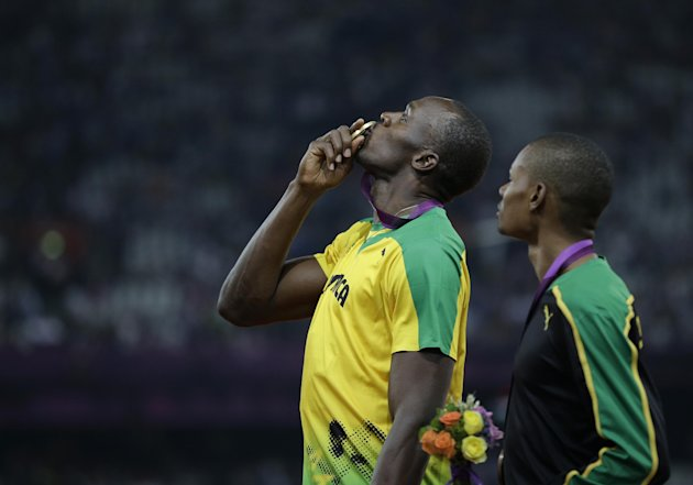 Jamaica's Usain Bolt kisses his gold medal as his teammate bronze medal winner Warren Weir, right, looks on during the ceremony for the men's 200-meter final during the athletics in the Olympic Stadium at the 2012 Summer Olympics, London, Thursday, Aug. 9, 2012. (AP Photo/Matt Slocum)