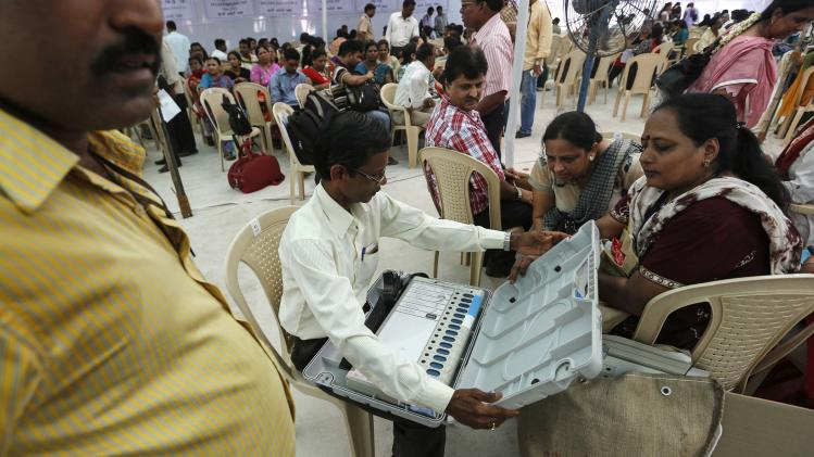 Election staff check electronic voting machine at distribution centre ahead of sixth phase of India's general election in Mumbai