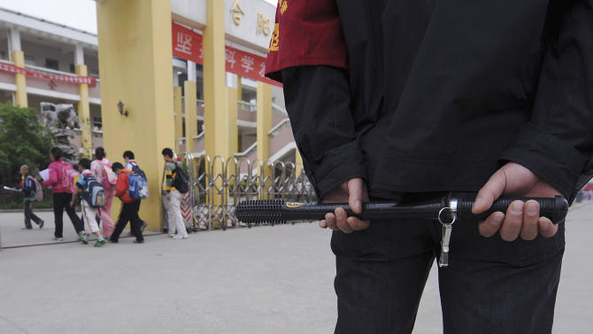 A security guard equipped with police baton stands at the entrance of a primary school in Hefei
