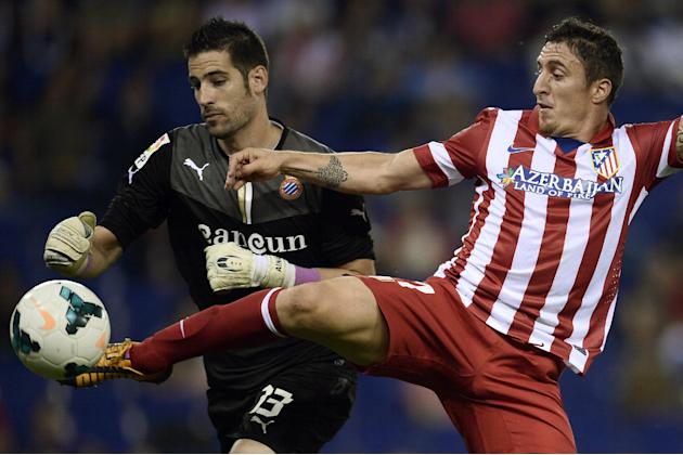 Atletico Madrid's Cristian Rodrguez, from Uruguay, right, duels for the ball against Espanyol's goalkeeper Kiko Castilla during a Spanish La Liga soccer match at Cornella-El Prat stadium in Cornella L