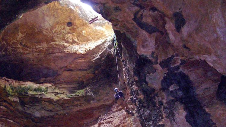 In an image provided by the Bureau of Land Management, date not known, Bureau of Land Management cave specialist Bryan McKenzie rappels into Natural Trap Cave in north-central Wyoming during a cleanup expedition. The cave holds the remains of tens of thousands of animals, including many now-extinct species, from the late Pleistocene period tens of thousands of years ago. Starting July 28, 2014, scientists plan to venture back into the cave and resume digging for the first time in more than 30 years. (AP Photo/Bureau of Land Management)