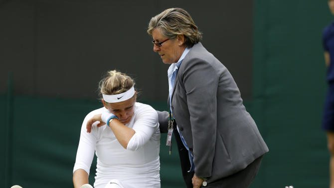 FILE - In this June 24, 2013 file photo, second-seeded Victoria Azarenka of Belarus, left, is attended to after taking a fall during her Women's first round singles match against Maria Joao Koehler of Portugal at the All England Lawn Tennis Championships in Wimbledon, London. Azarenka has pulled out of Wimbledon after hurting her right knee in her opening-round win. On Wednesday, June 26, 2013, minutes before her second-round match against Flavia Pennetta was to begin, she pulled out of the match. (AP Photo/Kirsty Wigglesworth, File)