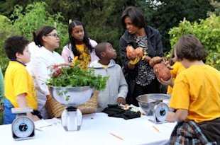 First Lady Michelle Obama, right, talks to White House Executive Chef Cristeta Pasia Comerford, second from left, as local 5th graders from Bancroft Elementary look on during the White House Kitchen Garden Fall Harvest on October 20, 2010, at the White House. The festival was part of the First Lady's initiative to stop childhood obesity. (Photo: Alex Wong/Getty Images)