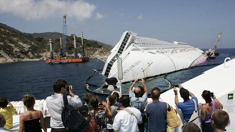 "Tourists take photographs of the Costa Concordia wreckage as they arrive on a ferry to the Giglio Island, Italy, Thursday, July 12, 2012. Works have begun to remove the tons of rocky reef embedded into the Concordia cruise ship's hull, a first step in plans to eventually tow the wreck away from the island, where it ran aground last January. The whole removal process could take as long as a year. In a broadcast interview Tuesday, Concordia's captain Francesco Schettino described the collision as a ""banal accident"" in which ""destiny"" played a role. (AP Photo/Gregorio Borgia)"